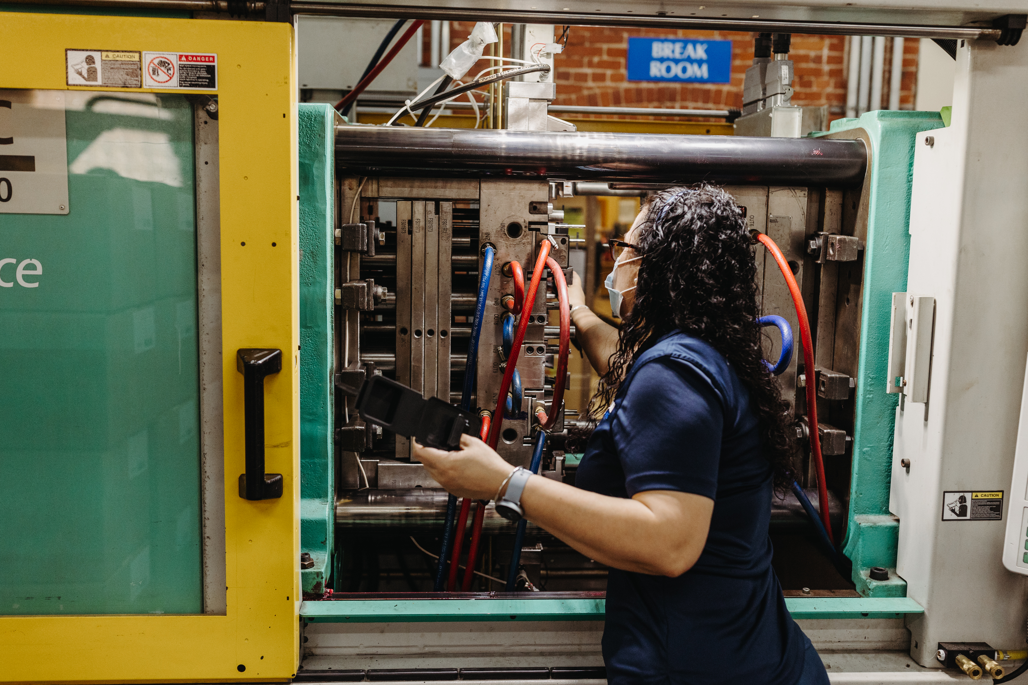 A woman (facing away from the camera) points at the wires in an injection molding machines