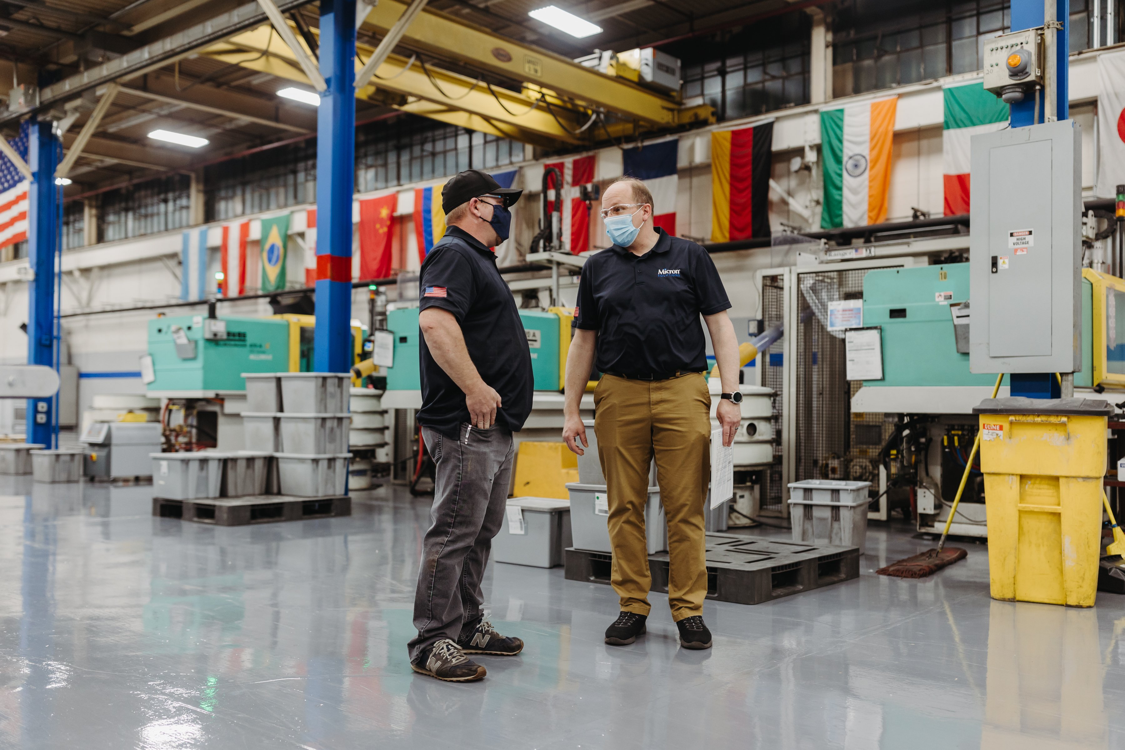Two men are talking to each other with injection molding machines behind them