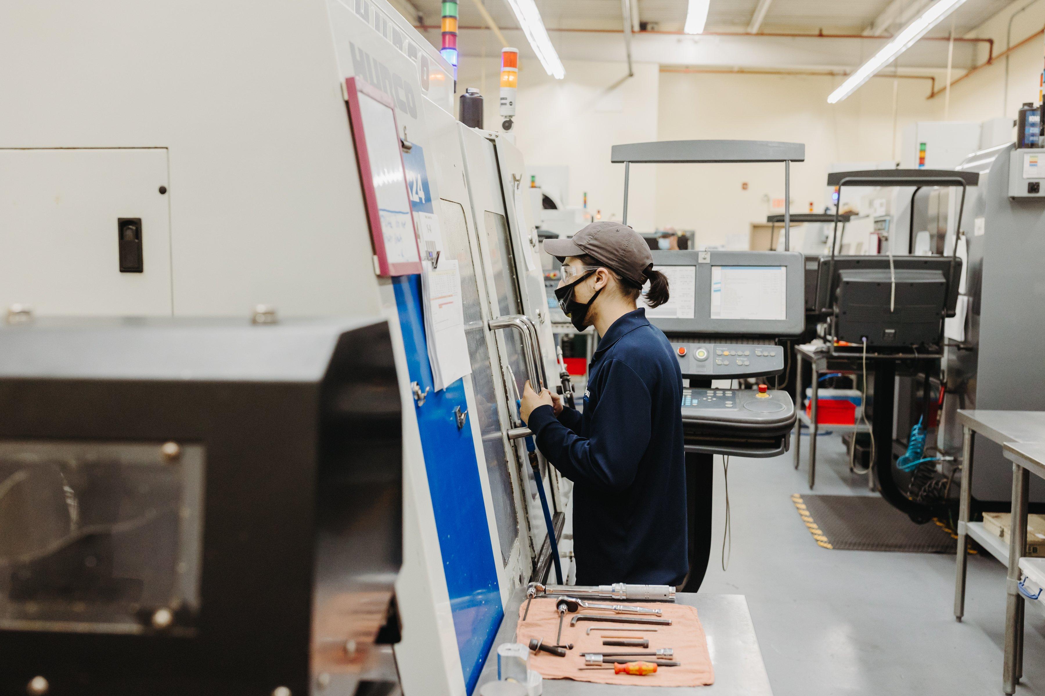 A man looks inside a CNC machine