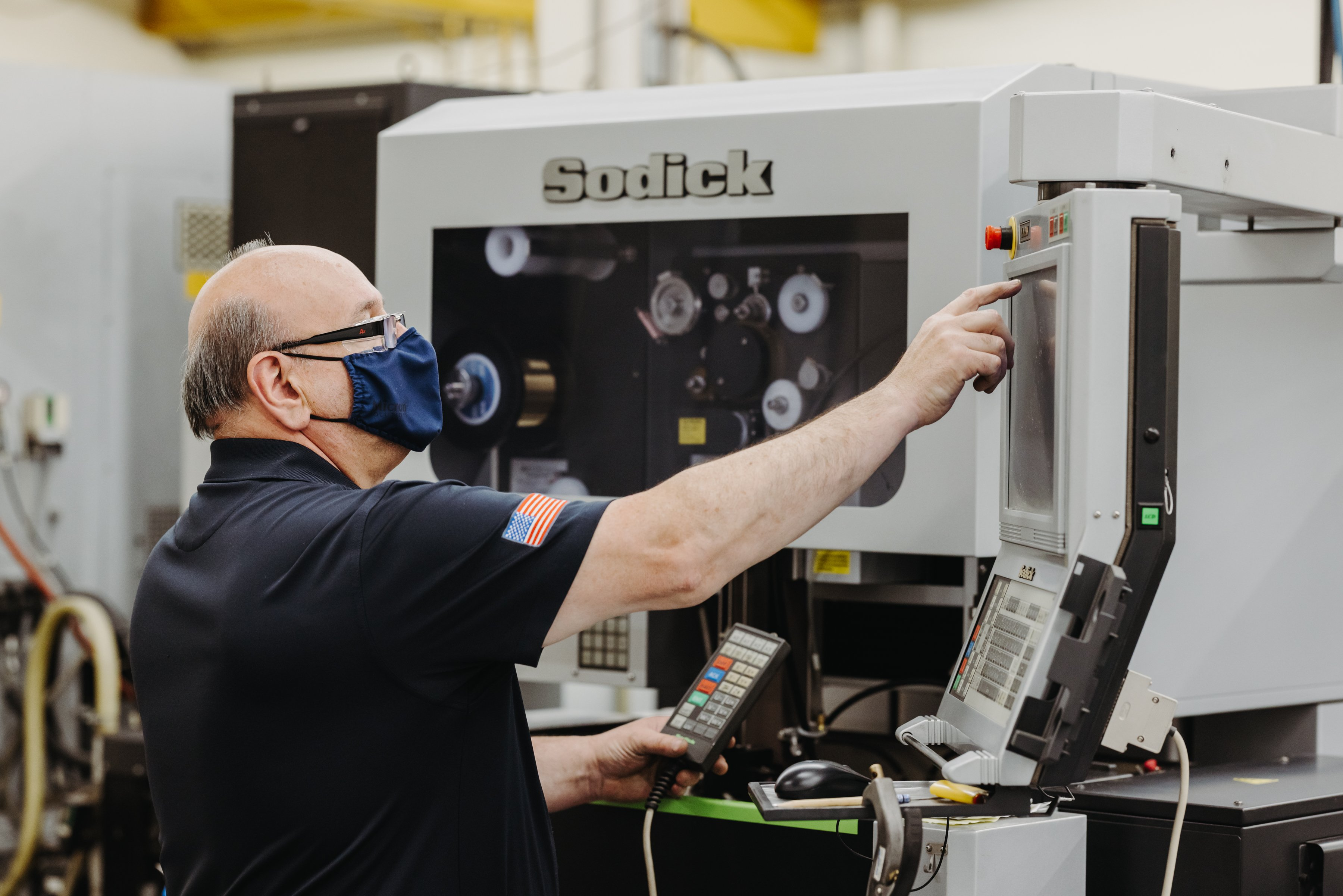 A man wearing a blue mask points to the screen of a CNC machine