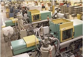 Two teal and yellow injection molding machines next to each other