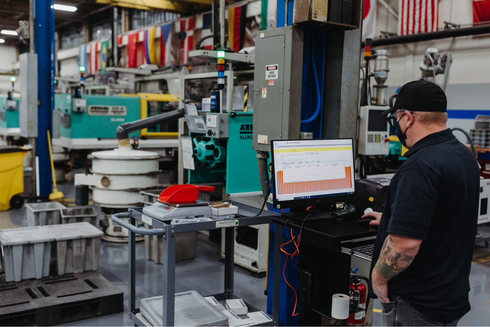 A man watches a screen that monitors the status of all Arburg injection molding machines