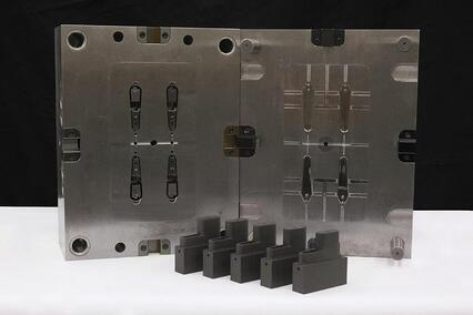 A metal mold standing behind 5 black injection-molded components made at Micron.