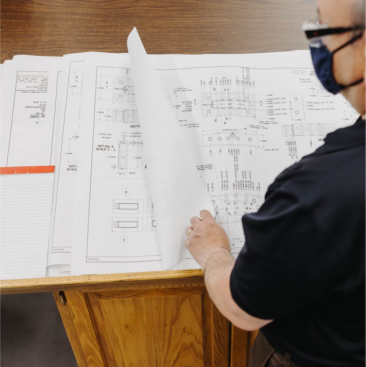 A man looks at pages of manufacturing blueprints