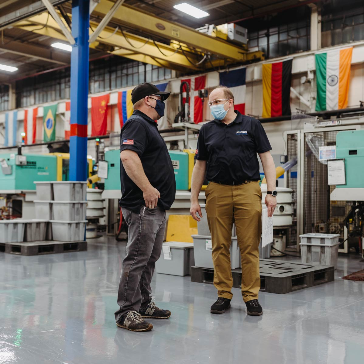 Two men talk to each other in front of a line of Arburg injection molding machines