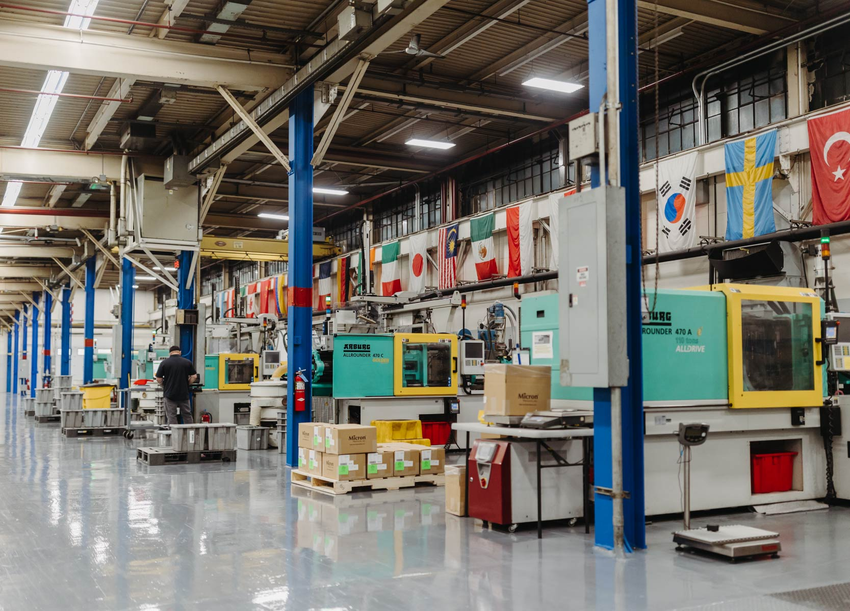 Four Arburg injection molding machines surrounded by flags of different countries