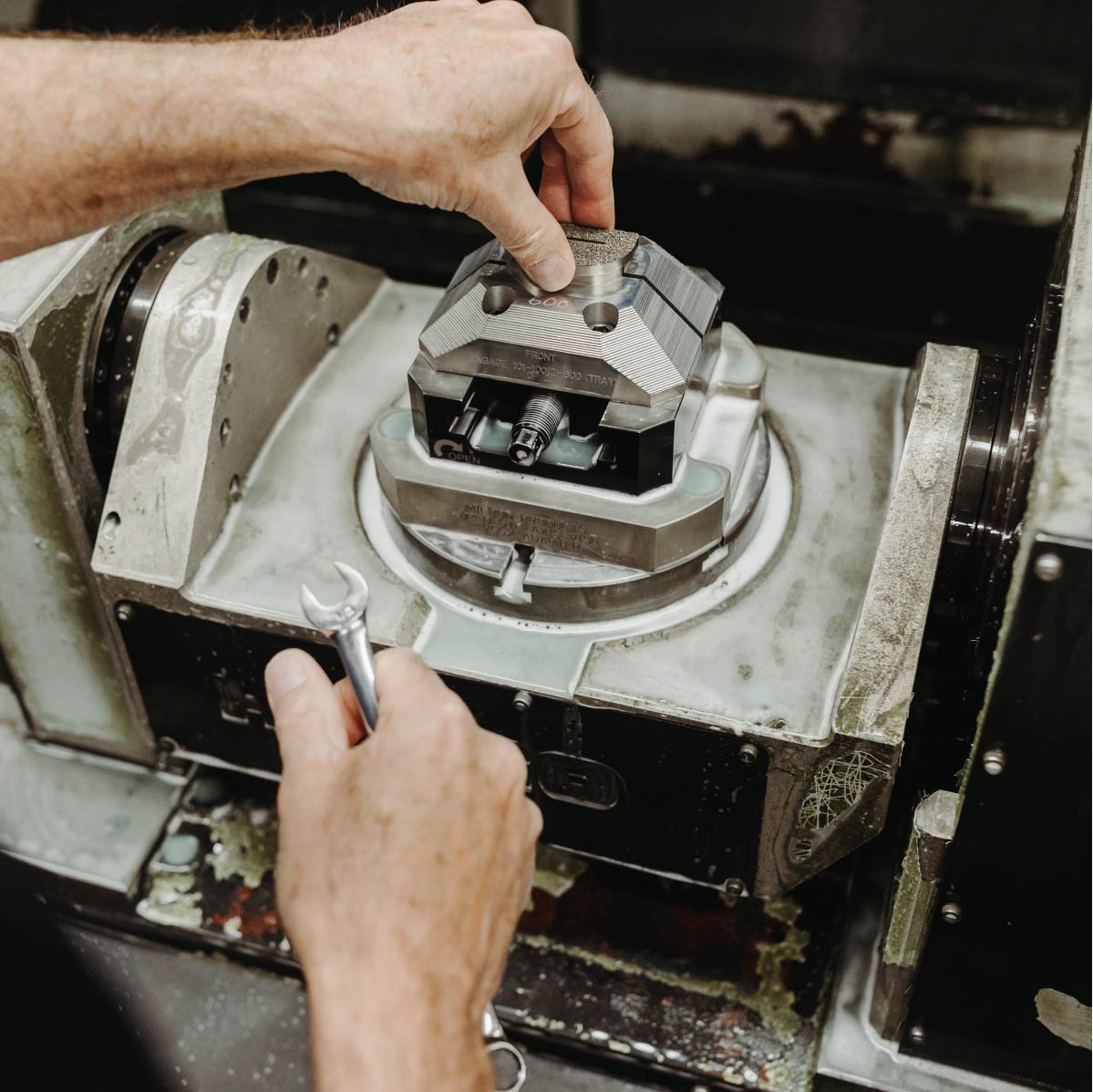 Close up of an employee holding a wrench and working on a product