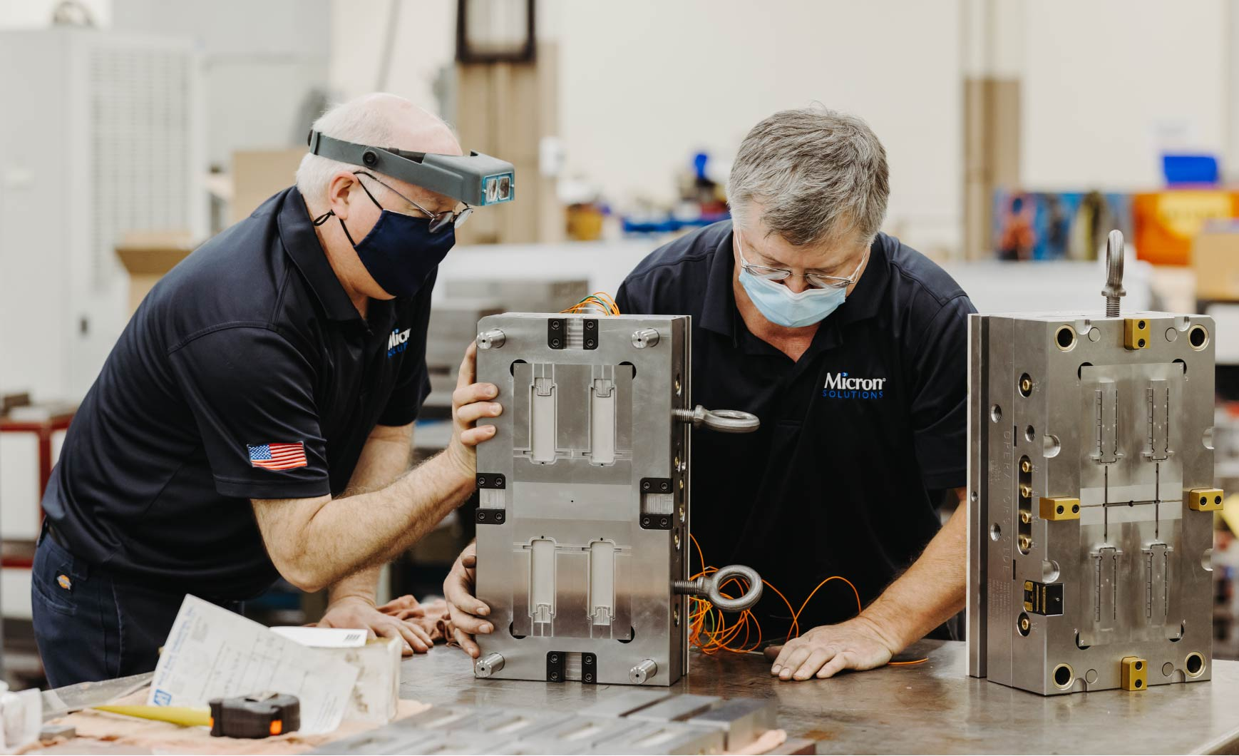 Two men wearing masks work on a mold