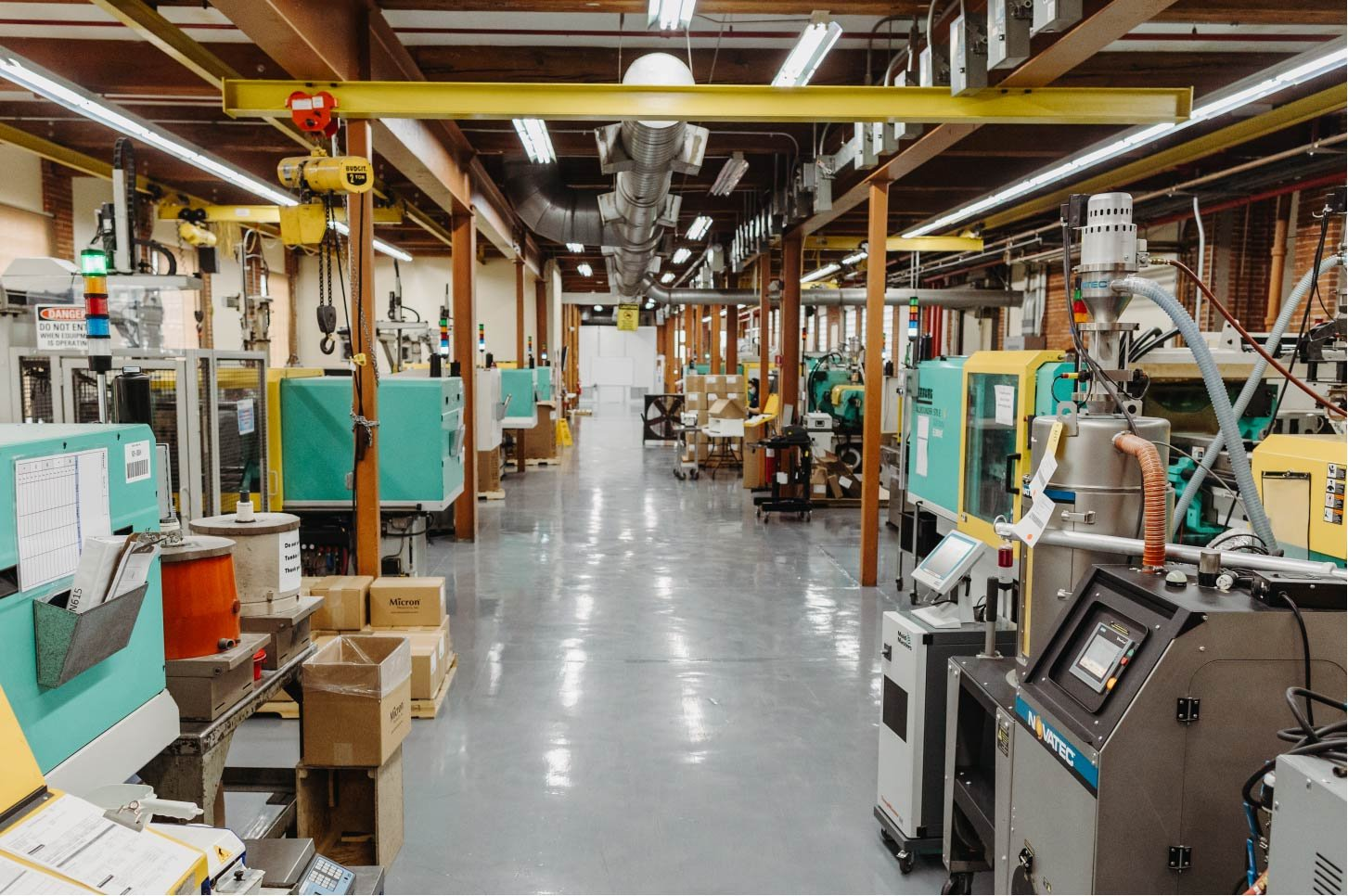 Manufacturing floor featuring two rows of Arburg injection molding machines